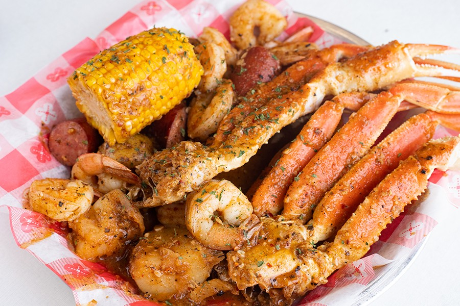 Spicy seafood boil with shrimp, crab legs, potatoes, sausage and corn. - MABEL SUEN