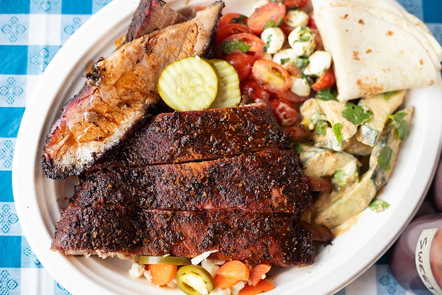A two-meat combo platter with brisket, ribs, tomato with smoked mozzarella, tortillas and cucumber with poblano ranch. - MABEL SUEN