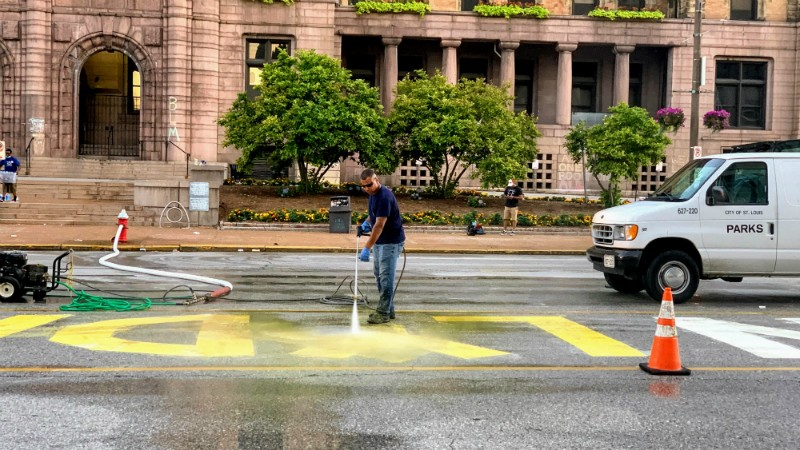 A city worker power washes the LYDA RESIGN painted sign from Tucker Boulevard. - DOYLE MURPHY