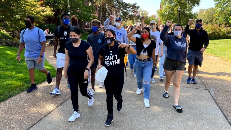 Vanessa Sarmiento (front left) and Ashlee Lambert (front right), lead the pack of student protestors down West Pine. - RILEY MACK