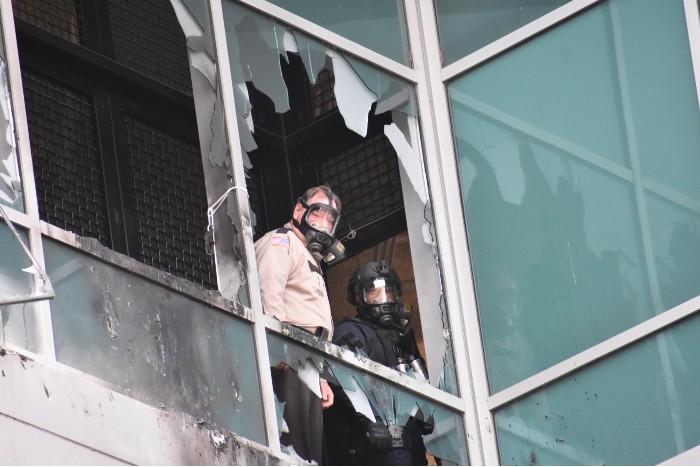 A St. Louis sheriff's deputy looks out the broken window of the jail. - DOYLE MURPHY