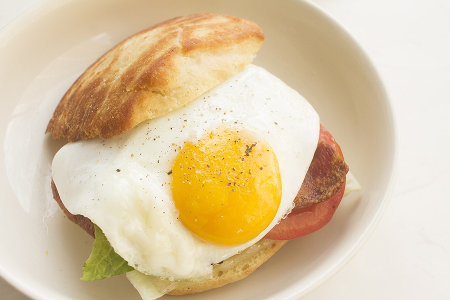 An English muffin sandwich with fried egg, bacon, Crystal aioli, red-pepper jelly and pepperjack. - PHOTO BY MABEL SUEN