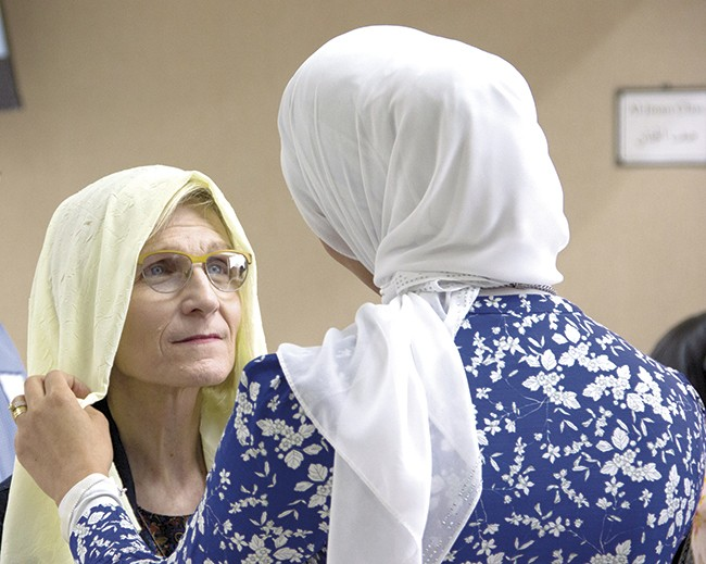 """A visitor tries on a headscarf during CAIR-Missouri's March 26 """"Make America Whole Again"""" open house. - PHOTO BY DANNY WICENTOWSKI"""