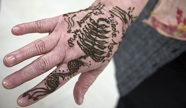 """At CAIR's open house, visitors could get henna tattoos, like this one urging people to """"Make America Whole Again."""" - PHOTO BY DANNY WICENTOWSKI"""