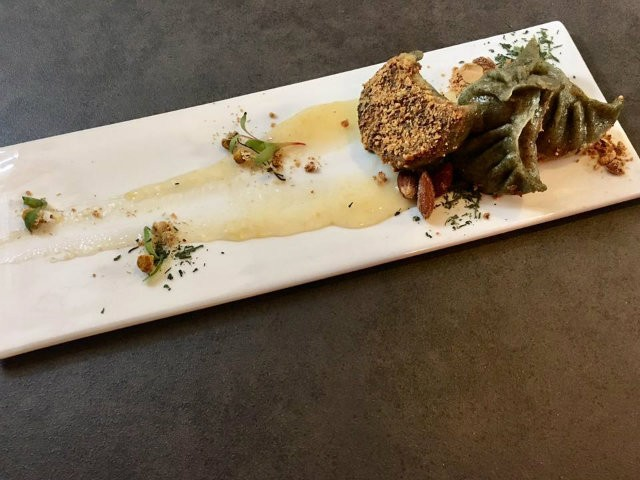 """A dessert potsticker, """"the Asian Cherry Bomb,"""" uses green tea matcha dough with a mascarpone pistachio filling and is finished with a lemon white tea sauce."""