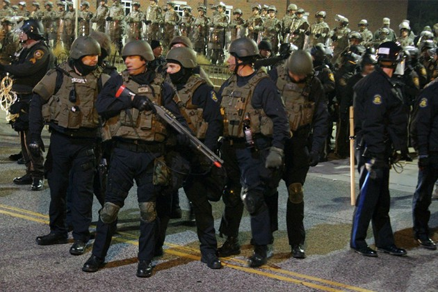 The Missouri National Guard stand in front of the Ferguson Police Department in 2014. - PHOTO BY DANNY WICENTOWSKI