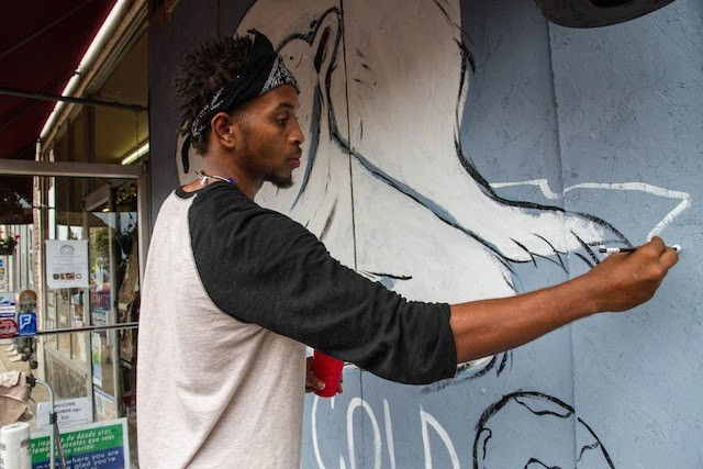 Artist Cornell McKay paints a polar bear on the plywood covering Plowsharing Crafts. - COURTESY OF PAINTING FOR PEACE IN FERGUSON, A CHILDREN'S BOOK