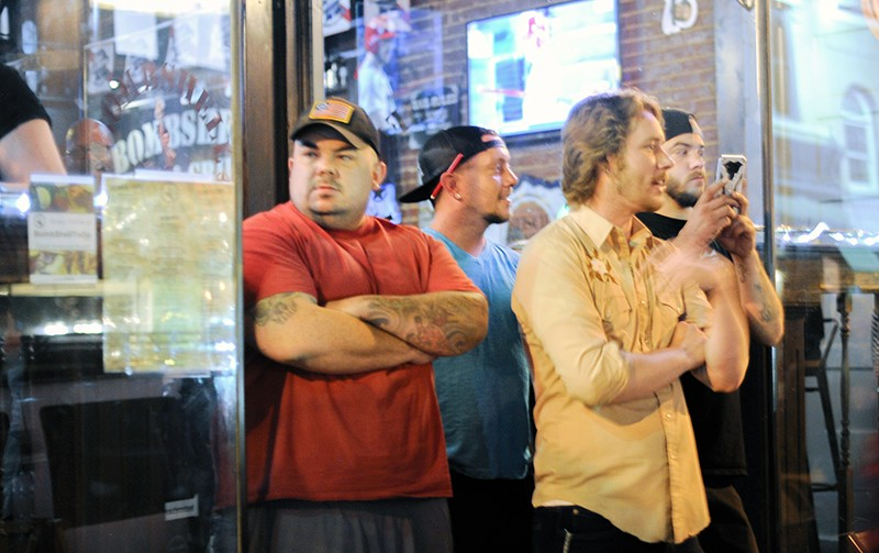 Bar patrons keep an eye on the protest marching by. - PHOTO BY KELLY GLUECK