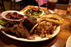 A combo plate with pulled pork, brisket and ribs with tangy slaw and roasted green beans with tomatoes.