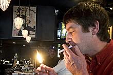 JENNIFER SILVERBERG - Bill Hannegan lights up an American Spirit in the bar of Herbie's Vintage 72.