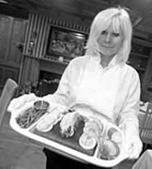 JENNIFER  SILVERBERG - Rockin' your dinner: Owner Earlene Acomb shows off - the Rose Garden's Stonegrill option.