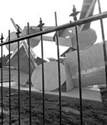 JENNIFER  SILVERBERG - Ernest Trova's sculpture, AV/Bedu, was given - to the city of St. Louis in 1979 but now stands on the - southwestern edge of Saint Louis University's midtown - campus. Trova's friends say the sculpture looks like - it's in the O.K. Corral because of the wrought-iron - fence surrounding it.