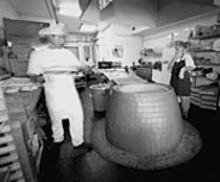 JENNIFER  SILVERBERG - Father-and-son team Edward (left) and Yuri Kiknadze make bread in Cafe Lavash's tandoor.