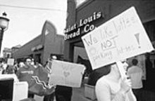 MARK  GILLILAND - Residents recently picketed the Bread Co. during the Saturday lunch rush in opposition to the planned demolition of two homes to create a parking lot.