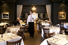 JENNIFER SILVERBERG - Server David Stiffelman minds the chic dining room at Chez Leon's new location in Clayton.