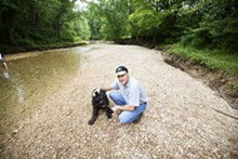 JENNIFER SILVERBERG - Steve Seyer and his giant schnauzer Dolphus on the gravel bed of Kiefer Creek in Castlewood State Park. Swimming in this water nearly killed the dog.