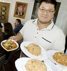 JENNIFER SILVERBERG - Simply Thai co-owner Scott Truong shows just a few of the 100 options on the menu.
