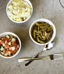 JENNIFER SILVERBERG - Three sides — potato salad, green beans with smoked turkey, and cucumber and tomato salad. See more photos from Flavors BBQ Sports Bar & Grill.