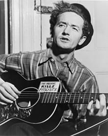 HOTOGRAPH BY AL AUMULLER. COURTESY OF THE WOODY GUTHRIE ARCHIVES. - Woody Guthrie in New York City, ca. 1943.