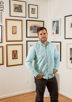 Adam Werth, president of the Print Club of Rochester, in Phillips Fine Art & Frame gallery, which houses the collection of the Print Club of Rochester. - PHOTO BY JOHN SCHLIA