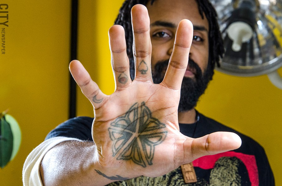 Adrien Moses Clark, a tattoo artist with Love Hate Tattoo, says the Flower City logo is a popular choice. He has one on his palm. - PHOTO BY MARK CHAMBERLIN