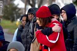 Alex Hare hugs family friend Mbele Badawi at the rally on Thursday evening. - PHOTO BY MATT DETURCK