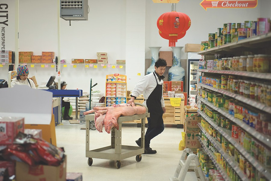 An employee moves pigs to the meat counter in Asia Food Market in Henrietta. - PHOTO BY THOMAS DOOLEY