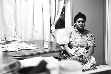 At center, Mukumbira's wife, Faduma Abdi, cradles her 1-month-old baby. Abdul Kadir. This is her eighth child. - GARY VENTURA
