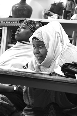 At right, Isha Abdi (left) and Khadija Ehow learn English at the Family Learning Center on Hart Street. - MATT WALSH