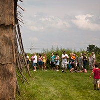 [ Slideshow ] Ganandogan Dance & Music Festival Attendees wait in line to enter a recreation of a 1650's longhouse at the Ganondagan historical site. PHOTO BY MATT BURKHARTT