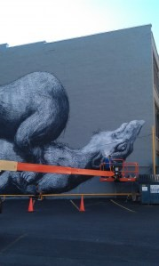 """Belgian artist ROA's mural for """"Wall\Therapy"""" is almost finished on the building facing the World Wide News lot at 100 St. Paul Street. PHOTO BY REBECCA RAFFERTY"""