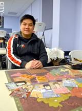 Game creator Nicholas Yu with his newest game, Eternal Dynasty. - PHOTO BY MATT DETURCK