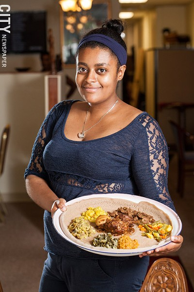 Herut Tekilu with the Special #1 platter of vegetable and meat dishes at Abyssinia. Herut recently returned to Rochester from New York City to help her aunts run Abyssinia. - PHOTO BY JOHN SCHLIA