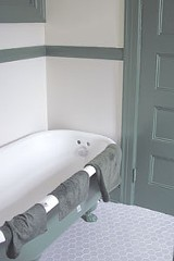 In a small bathroom, the clawfoot tub and 100-year-old - molding were saved and reinstalled; the walls and floor are new.