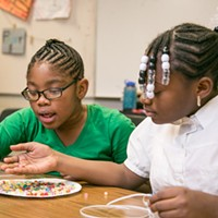 SWAN After-School Program Jaila & Tavariana dig through a plate of beads for their projects. PHOTO BY MIKE HANLON
