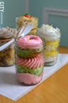 Jarred cakes, including pistachio with strawberry icing (center).