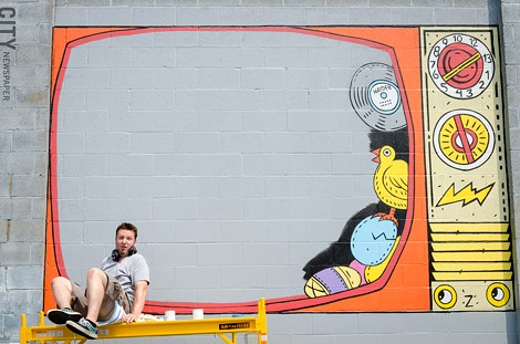 John Perry works on his piece in the Public Market. - PHOTO BY MARK CHAMBERLIN
