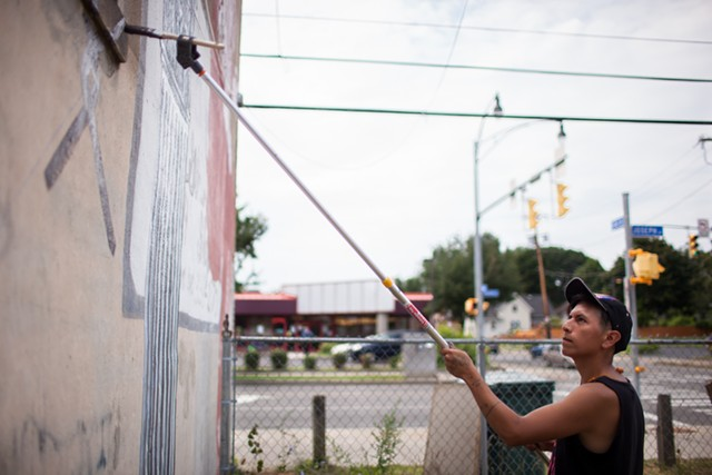 "LNY adds a chain link fence to his mural at 852 Joseph Avenue, which also features a portrait of Frederick Douglass. ""When you're working in a city, you're using the city, the history, as a medium,"" he says."