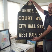 Local Memorabilia Mike Governale with an original Rochester subway destination roll. PHOTO BY KATHERINE STATHIS