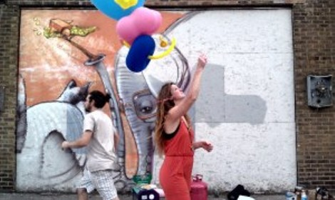 """New York City artist Cern's whimsical mural on Pennsylvania Avenue is complemented by the balloon sculptures he created for visitors during the """"Wall/Therapy"""" block party Sunday afternoon. PHOTO BY REBECCA RAFFERTY"""