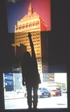 "Tara Merenda Nelson's ""End of Empire"" (seen here with a viewer's silhouette) is a projected collage of the Kodak tower using four formats of film. Nelson's show, ""Light Sensitive,"" is currently on view at Visual Studies Workshop."