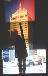 "PHOTO PROVIDED - Tara Merenda Nelson's ""End of Empire"" (seen here with a viewer's silhouette) is a projected collage of the Kodak tower using four formats of film. Nelson's show, ""Light Sensitive,"" is currently on view at Visual Studies Workshop."