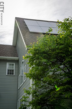 The solar panels on Cynette Cavaliere's Penfield home provide enough electricity to offset the power she uses to charge her Chevy Volt. - PHOTO BY MARK CHAMBERLIN