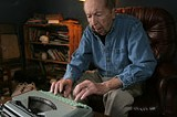 PHOTO BY GARY VENTURA - The typewriter close to his knees: life-long local sportswriter George Beahon.