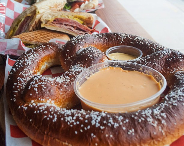 A sizable pretzel with cheese sauce and mustard at TinRoof Bar & Grill. - PHOTO BY JACOB WALSH