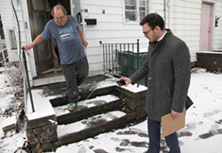Wayne Russell, who is Linda Barger's brother, points out their landlord's attempt at fixing their front porch, while Mike Furlano, an attorney with the Legal Aid Society of Rochester, photographs it. - PHOTO BY MAX SCHULTE