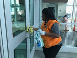 A worker disinfects the doors and handles at the Rochester Transit Center. - PHOTO BY DAVID ANDREATTA
