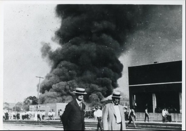 Two people stand near the railroad tracks across the street from a burning building during the 1921 Tulsa Race Massacre. The background shows a group of people standing and watching the building burn. - PHOTO COURTESY OF TULSA HISTORICAL SOCIETY & MUSEUM