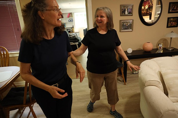 Patty Starr, who is deafblind, holds the arm of interpreter Elisa Mlynar as they walk in Starr's home. - PHOTO CREDIT MAX SCHULTE