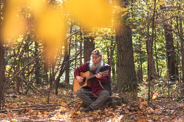 Bob Bunce plays the guitar on his rural property near Groveland, New York. - PHOTO BY RYAN WILLIAMSON